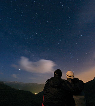 A couple enjoys watching the night sky